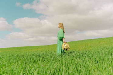 Blond young woman wearing green dress standing on a field - ERRF03298