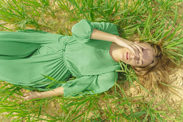 Blond young woman wearing green dress lying on a field with eyes closed - ERRF03301