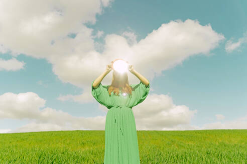 Young woman wearing green dress standing on a field holding reflecting mirror - ERRF03310
