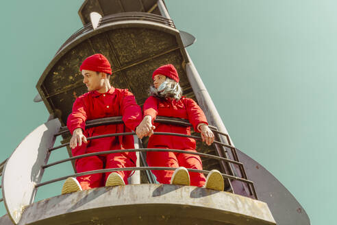 Young couple wearing red overalls and hats standing on platform looking at distance - ERRF03349
