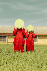 Young couple wearing red overalls  standing on a field hiding faces behind green circle - ERRF03352
