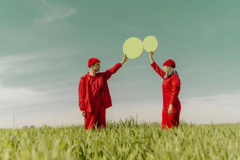 Young couple wearing red overalls  standing on a field holding two green circles - ERRF03355