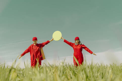 Young couple wearing red overalls and hats standing on a field holding green circle - ERRF03358