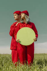 Young couple wearing red overalls and hats standing on a field with green circle - ERRF03361