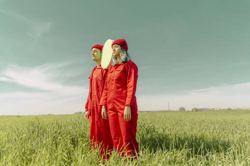 Young couple wearing red overalls  standing on a field with green circle - ERRF03364
