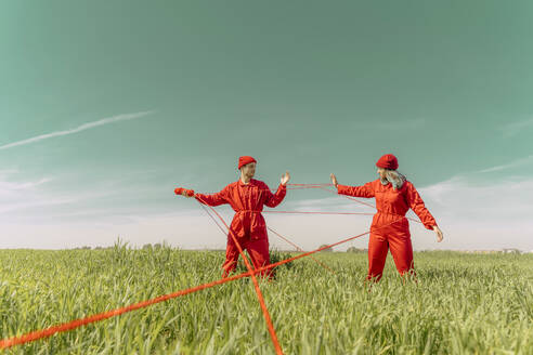 Young couple wearing red overalls and hats performing on a field with red string - ERRF03367