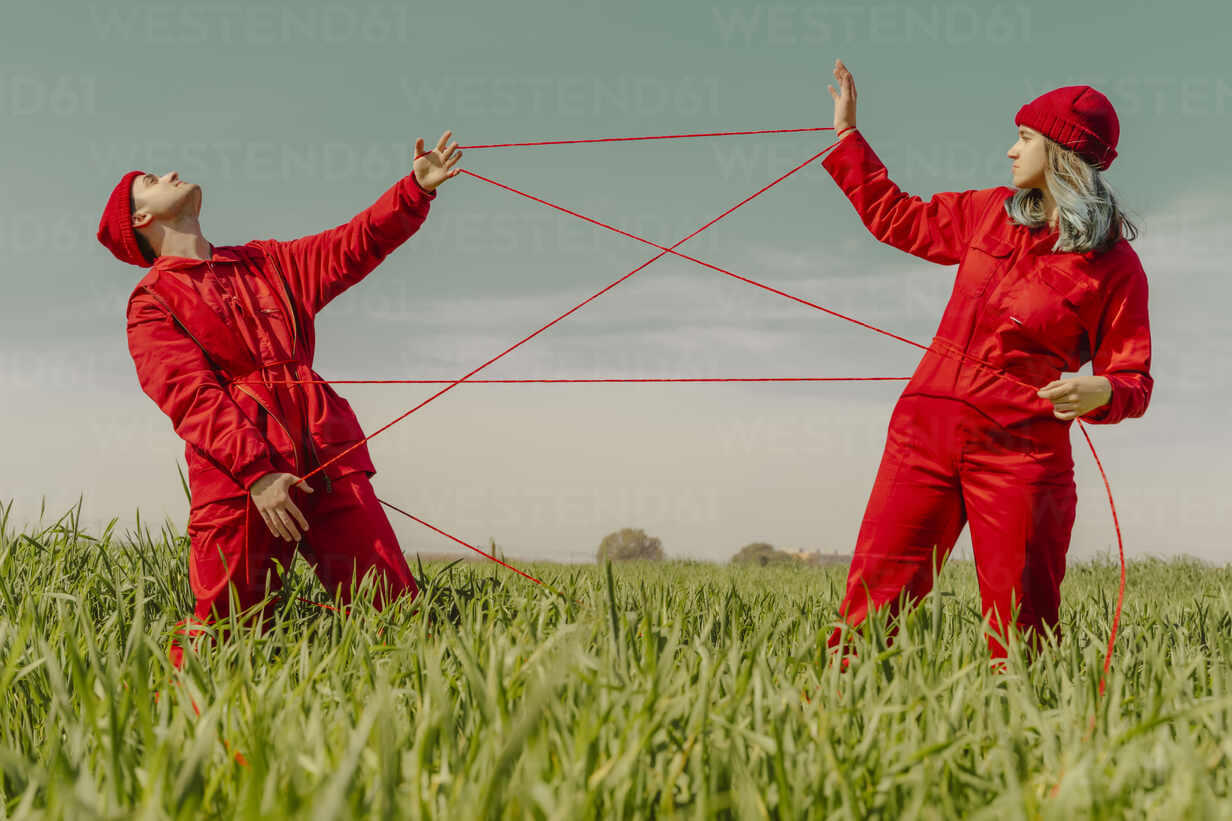 Young couple wearing red overalls and hats performing on a field with red string - ERRF03370 - Eloisa Ramos/Westend61