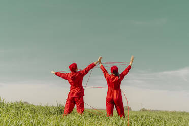 Back view of young couple wearing red overalls and hats performing on a field with red string - ERRF03373