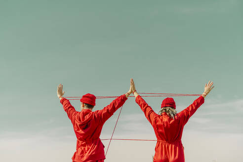 Back view of young couple wearing red overalls and hats performing with red string outdoors - ERRF03376