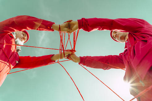 Crop view of young couple dressed in red performing with red string against sky - ERRF03382