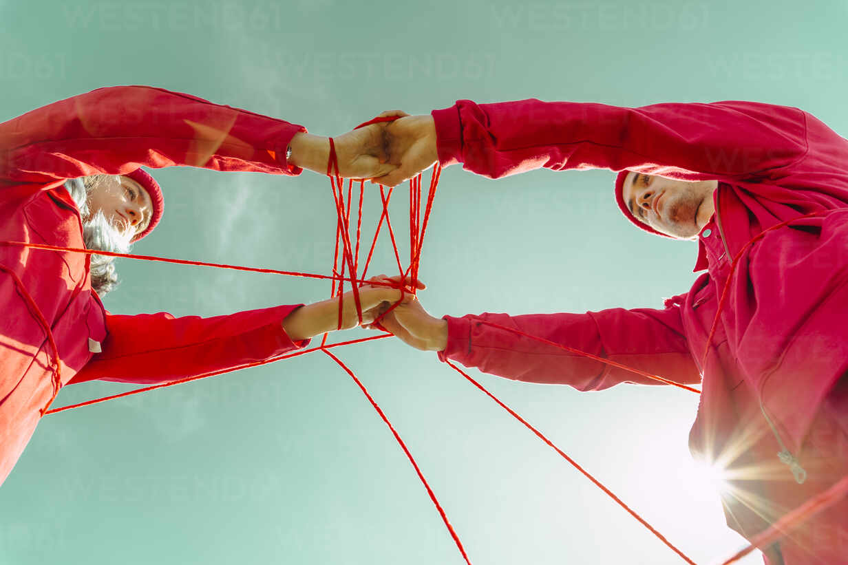 Crop view of young couple dressed in red performing with red string against sky - ERRF03382 - Eloisa Ramos/Westend61