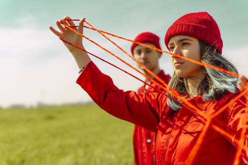 Portrait of young woman dressed in red performing with red string outdoors - ERRF03385