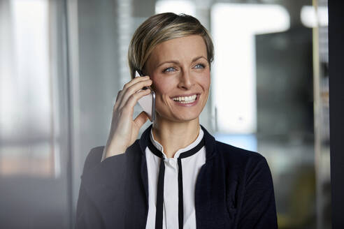 Portait of happy businesswoman on the phone in office - RBF07379