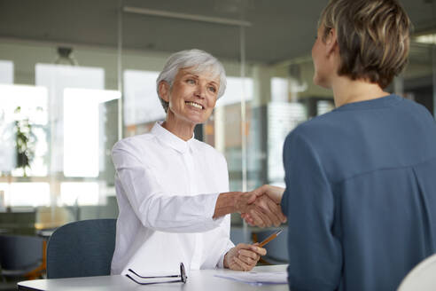 Two businesswomen shaking hands at desk in office - RBF07424