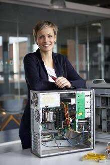 Portrait of smiling woman assembling desktop pc in office - RBF07448