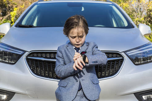 A six year old boy leaning on car, looking at his watch - MINF14506