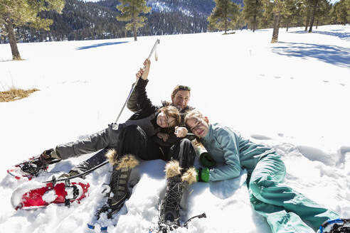 A woman and her two children, teenage girl and a young boy lying in the snow in snow shoes and ski gear. - MINF14554