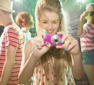 Playful teenage girl using digital camera at party - FSIF04644