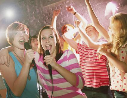 Happy teenage friends singing karaoke at party - FSIF04647