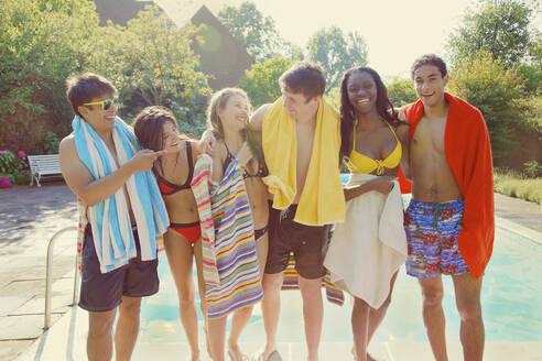 Portrait happy teenage friends at sunny summer poolside - FSIF04659