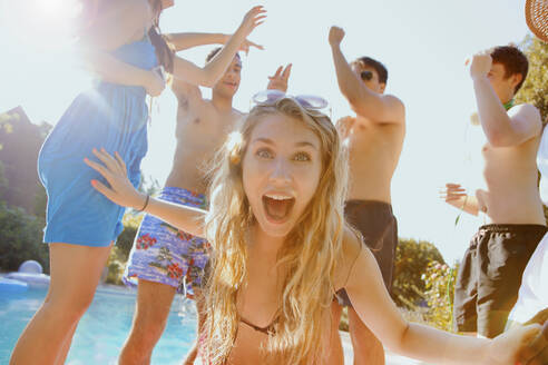 Portrait exuberant teenage girl dancing with friends at sunny summer poolside - FSIF04665