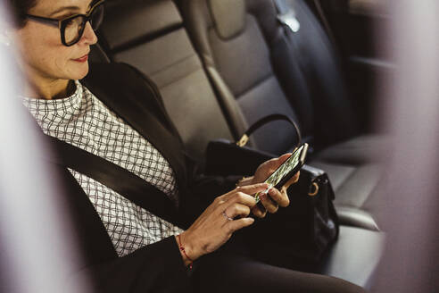 Female entrepreneur using device screen while sitting in car - MASF17603
