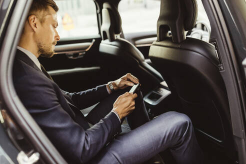Side view of businessman using smart phone while sitting in car - MASF17612