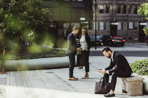 Businessman showing smart phone to female colleague while male coworker surfing net outdoors - MASF17639