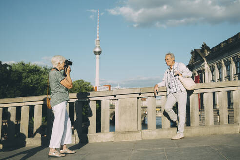 Full length of woman taking photograph of senior man while standing on bridge against tower in city - MASF17666