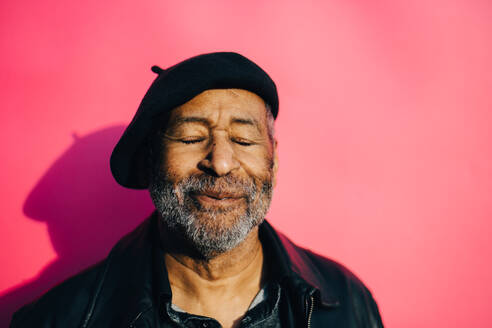 Smiling senior man with eyes closed against pink background - MASF17759