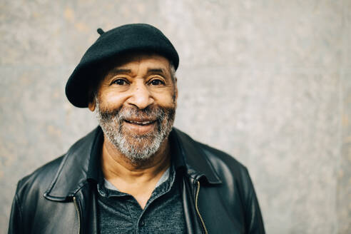 Portrait of smiling senior man against wall - MASF17762