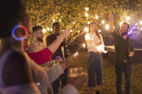 Playful friends with sparklers enjoying garden party - CAIF25991