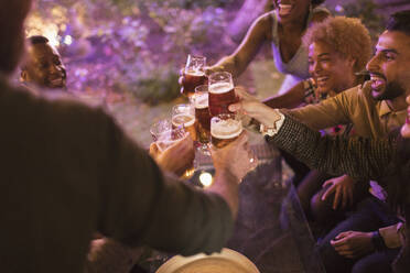 Friends toasting beer glasses at garden party - CAIF26000