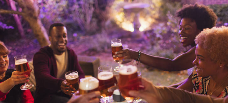 Friends toasting beer glasses at party - CAIF26018