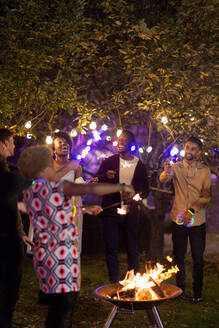 Happy friends with sparklers around fire pit at garden party - CAIF26021