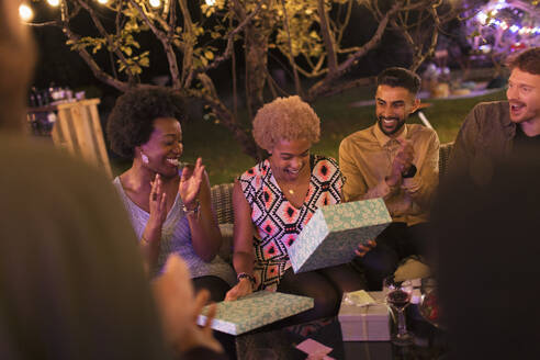 Friends watching woman open birthday gift at garden party - CAIF26027