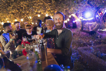 Portrait happy man bartending for friends at garden party - CAIF26030