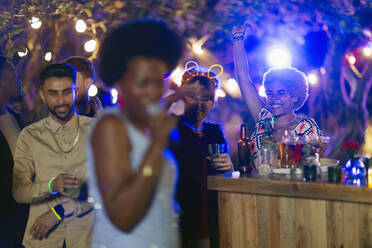 Friends dancing and drinking at garden party - CAIF26033