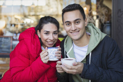 Portrait happy young couple drinking coffee at sidewalk cafe - CAIF26042