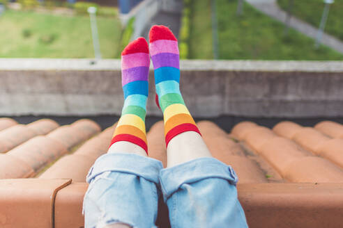 Crop view of woman sitting on rooftop wearing colourful striped socks - FVSF00047