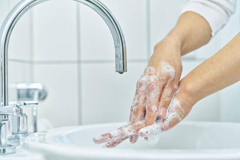 Woman washing her hand with soap - DIKF00408