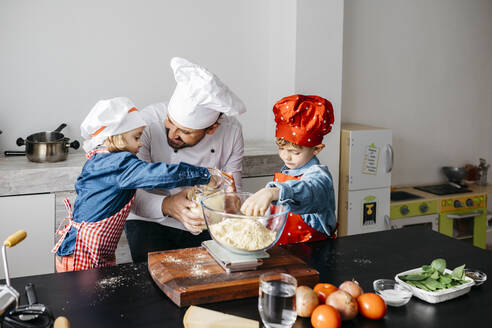 Father with two kids preparing dough for homemade gluten free pasta in kitchen at home - JRFF04268
