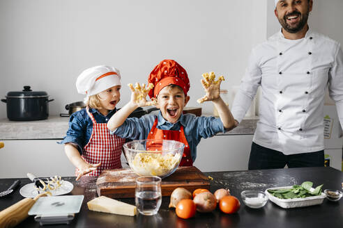 Portrait of happy kids preparing dough with father in kitchen at home - JRFF04274