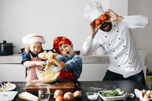 Playful father with two kids covering his eyes with tomatoes in kitchen - JRFF04277