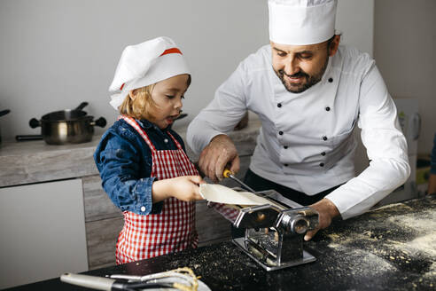 Father and daughter making homemade pasta with pasta machine in kitchen at home - JRFF04292