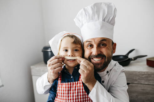 Playful father with daughter having fun while preparing homemade pasta in kitchen at home - JRFF04301