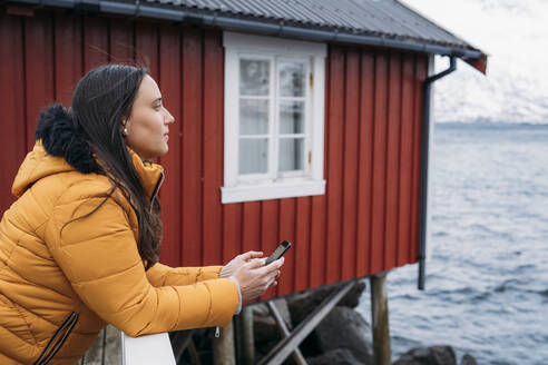 Tourist with cell phone at a hut at the coast, Lofoten, Norway - MPPF00709