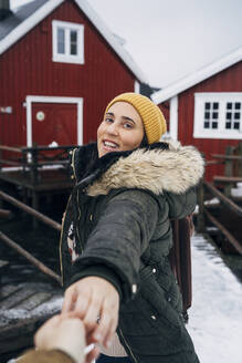 Portrait of smiling tourist holding man's hand at a hut, Lofoten, Norway - MPPF00736