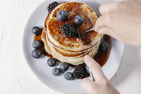 Woman about to cut a slice of a stack of pancakes with berries and syrup - CAVF78565