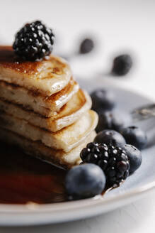 Close up of a fluffy homemade pancakes with syrup and berries - CAVF78571